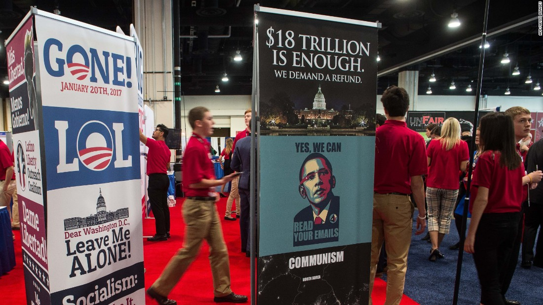 Volunteers walk by a stand at the annual Conservative Political Action Conference.