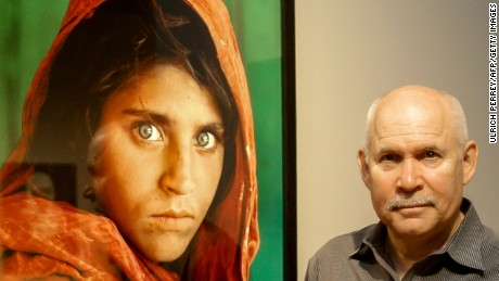 "Photographer Steve McCurry poses next to his photos of the ""Afghan Girl"" named Sharbat Gula at the opening of the ""Overwhelmed by Life"" exhibition at the Museum for Art and Trade in Hamburg, Germany in 2013."
