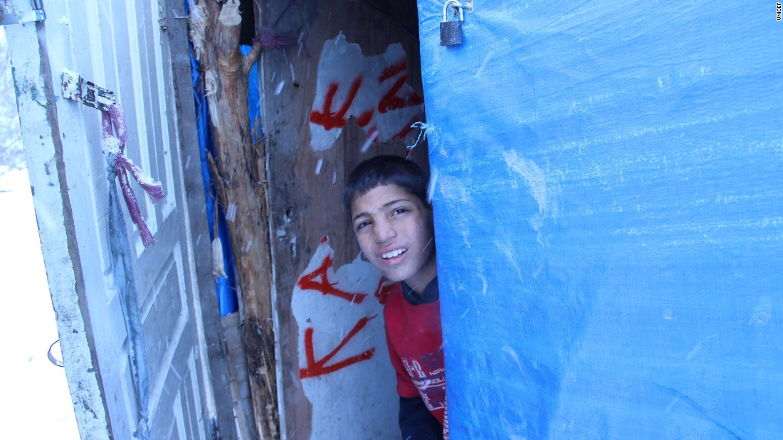 Khalil looks out from the doorway of his family's tent shelter, in a host community in Dikmen Valley, Turkey.   UNICEF has reached millions of Syrians inside and outside Syria.