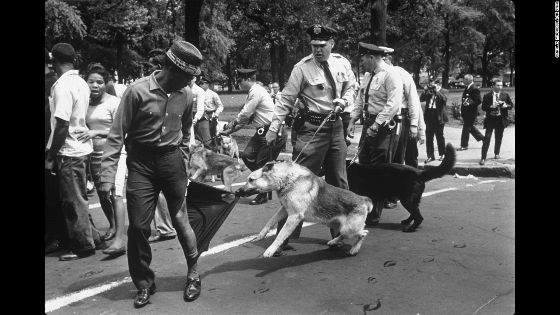 "A man looks calmly over his shoulder as a police dog in Birmingham rips his trouser leg in 1963. ""The figure in the photo is a perfect symbol of nonviolence,"" Kasher said. ""You know, the man is standing there, taking it, not fighting back, amid this incredible rush of hatred and violence and as another dog is charging right at Moore's -- at the viewer's -- face."""