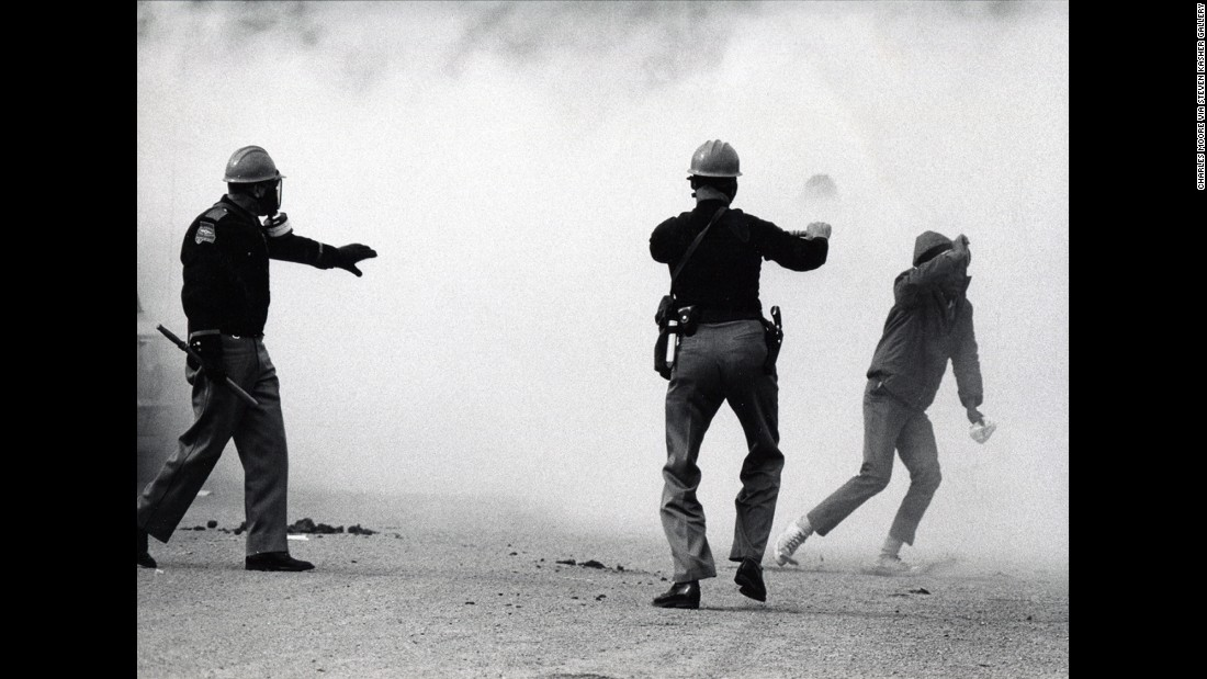 "Alabama state troopers wear gas masks as tear gas is fired on marchers in 1965. Fifty years ago, about 600 people began a 50-mile march from Selma, Alabama, to the state capital of Montgomery so that they could protest discriminatory practices that prevented black people from voting. But as the marchers descended to the foot of the Edmund Pettus Bridge, state troopers used brutal force and tear gas to push them back. It is now known as ""Bloody Sunday."""
