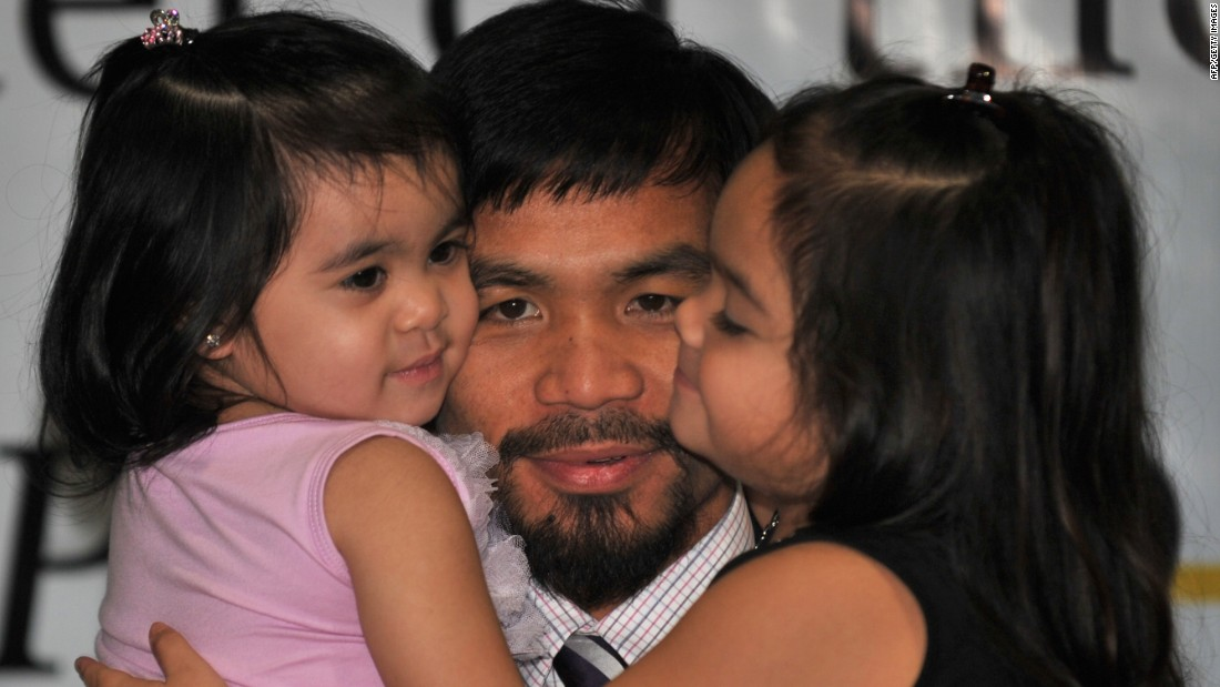 The Filipino superstar hugs his daughters Princess (R) and Queen Elizabeth during a press conference in Manila on November 20, 2010. Family snaps make up much of his Instagram feed.