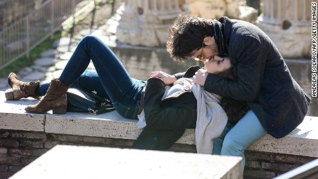 A couple exchange a kiss in front of the Ancient Foro Romano in central Rome, on February 7, 2014.  AFP PHOTO / ANDREAS SOLARO        (Photo credit should read ANDREAS SOLARO/AFP/Getty Images)