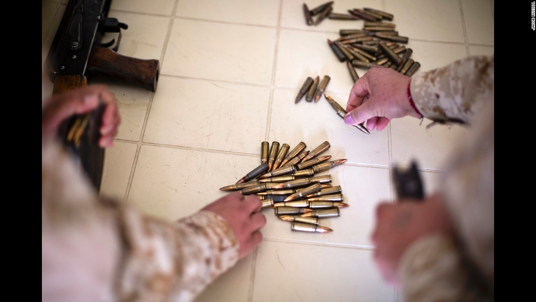 Female Peshmerga load rifle magazines.