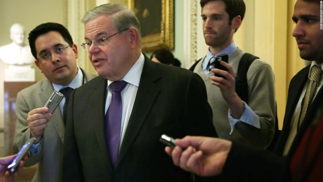 Sen. Robert Menendez talks to reporters as he arrives at the weekly Senate Democratic Policy Committee luncheon March 25, 2014 at the Capitol in Washington.