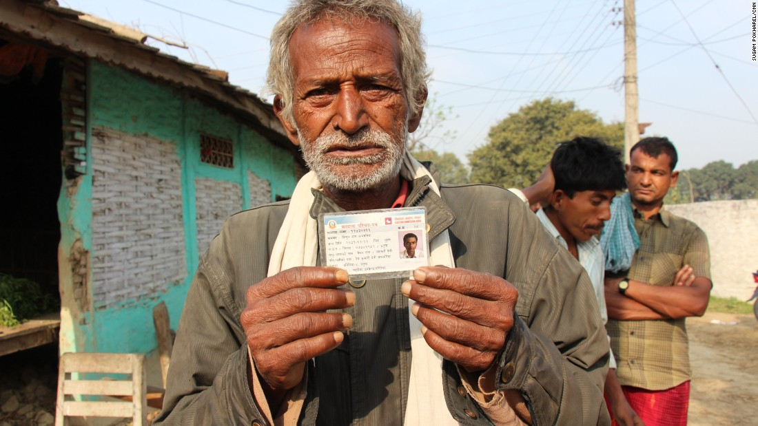 The father of Kishun Das holds up his son's ID.
