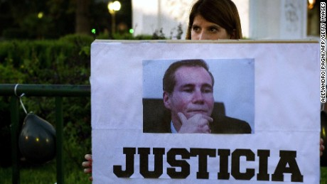 "A woman holds a sign reading ""Justice"" during a demo at Mayo square, in Buenos Aires on January 26, 2015, demanding justice in the death of Argentine public prosecutor Alberto Nisman --who was found dead in his home on January 18-- just hours before a congressional hearing to allegedly present evidence against President Cristina Fernandez de Kirchner of shielding Iranian officials implicated in a bomb attack on a Jewish community center in 1994 that left 85 dead. President Cristina Fernandez just announced during a national simultaneous broadcast she will disband Argentina's intelligence service ""and create a Federal Intelligence Agency"" with a leadership chosen by the president but subject to Senate approval"""