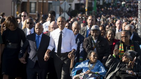 US President Barack Obama walks alongside Amelia Boynton Robinson (R), one of the original marchers, the Reverend Al Sharpton (2nd R), First Lady Michelle Obama (L), and US Representative John Lewis (2nd-L), Democrat of Georgia, and also one of the original marchers, across the Edmund Pettus Bridge to mark the 50th Anniversary of the Selma to Montgomery civil rights marches in Selma, Alabama, March 7, 2015. The event commemorates Bloody Sunday, when civil rights marchers attempting to walk to the Alabama capital of Montgomery to end voting discrimination against African Americans, clashed with police on the bridge. AFP PHOTO / SAUL LOEB (Photo credit should read SAUL LOEB/AFP/Getty Images)