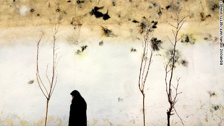 An Iranian woman walks past a wall in Tehran on March 8, 2015, bearing stains of exploded fire crackers from last years Fire feast, or Chaharshanbeh Soori, held annually on eve of the last Wednesday before the Persian new year of Noruz. Noruz is the new year according to the Persian solar calendar and is a Zoroastrian tradition, still celebrated by Iranians even after Islam. Noruz will be celebrated this year on 21st of March.