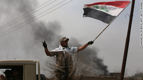 "Smoke billows in the background as a member of the Iraqi paramilitary Popular Mobilisation units flashes the ""V"" for victory sign after regaining control of the village of Albu Ajil, near the city of Tikrit, from jihadists of the Islamic State (IS) group, on March 9, 2015. Some 30,000 Iraqi soldiers, police and the increasingly influential paramilitary Popular Mobilisation units, which are dominated by Shiite militias, have been involved in a week-old operation to recapture Tikrit, one of the jihadists' main hubs since they overran large parts of Iraq nine months ago.  AFP PHOTO / AHMAD AL-RUBAYE        (Photo credit should read AHMAD AL-RUBAYE/AFP/Getty Images)"