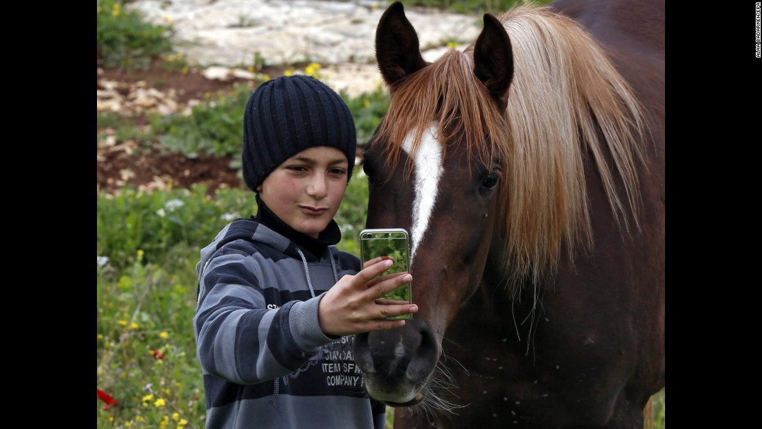 A boy takes a photo with a horse at his family farm near the West Bank city of Nablus on Wednesday, March 4.