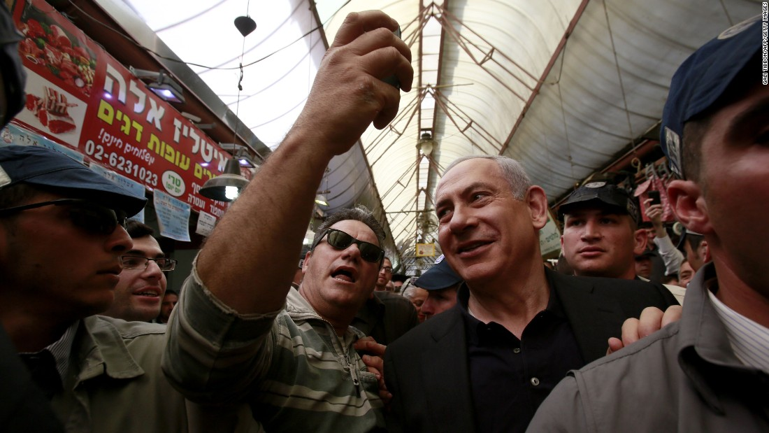 A man takes a selfie with Israeli Prime Minister Benjamin Netanyahu as Netanyahu campaigns at a Jerusalem market on Monday, March 9.