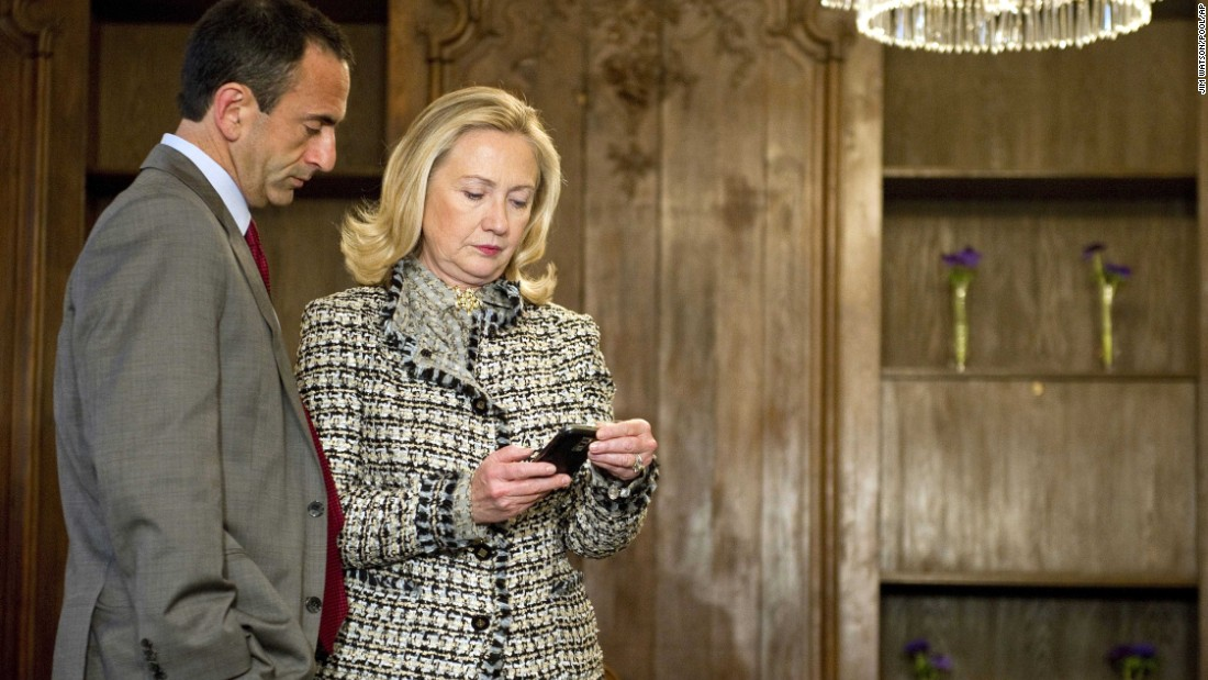 Clinton looks at a phone with Assistant Secretary of State for European Affairs Philip Gordon as they wait in a Munich, Germany, conference room for a bilateral meeting with the Ukrainian President in February 2012.
