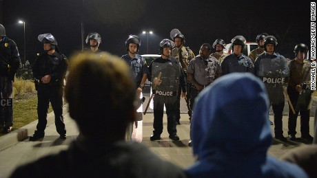 Police officers stand on alert during the protests on March 11.