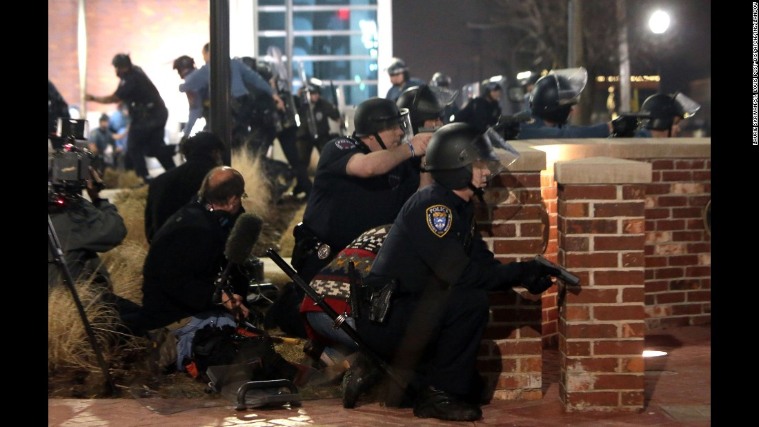 Police take cover after the two officers were shot on March 12.