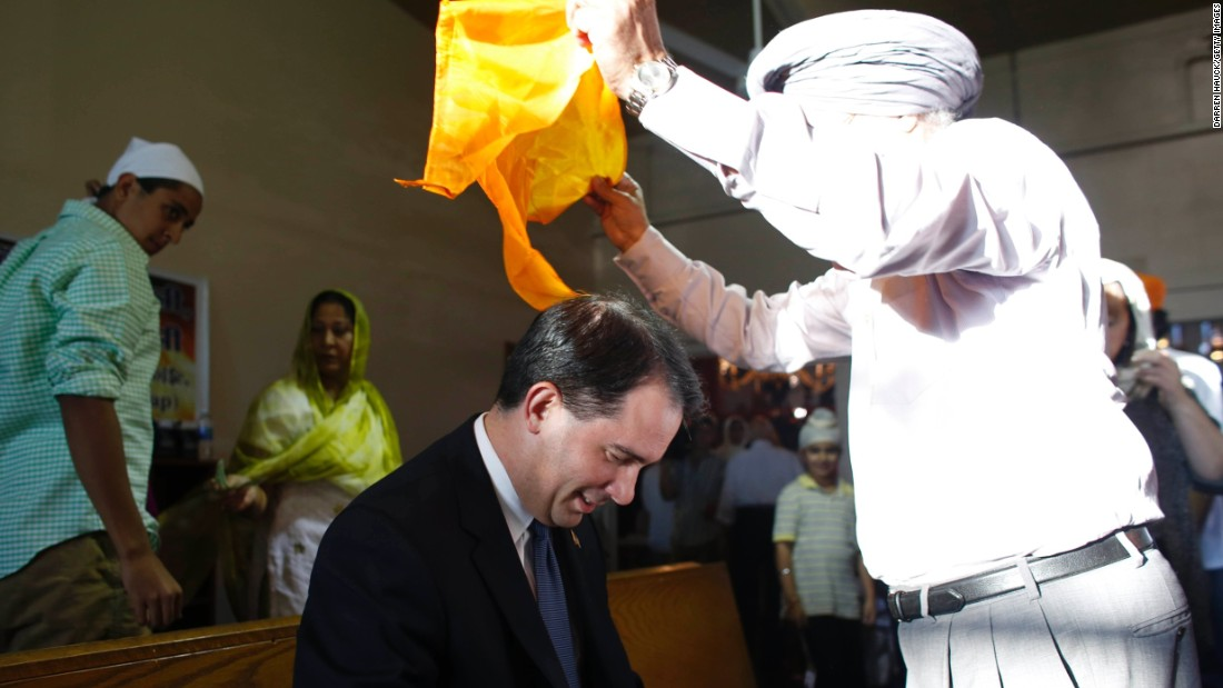 Walker has a scarf put on his head during a special service at the Sikh Religious Society of Wisconsin for the victims of the shooting at the Sikh Temple of Wisconsin the previous day, on August 6, 2012, in Brookfield, Wisconsin.