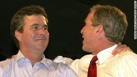 Brothers former Florida Gov. Jeb Bush (left) and former U.S. President George W. Bush stand with their arms around each other's shoulders at a rally in Miami, Florida September 22, 2000.
