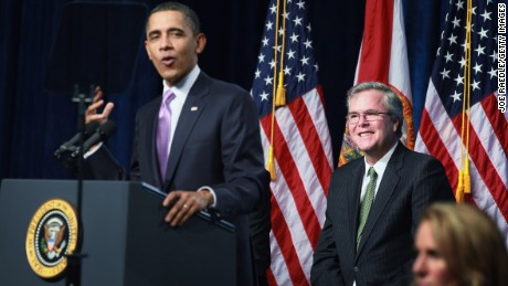 U.S. President Barack Obama (left) speaks about former Florida Governor Jeb Bush (center) while visiting Miami Central Senior High School on March 4, 2011 in Miami, Florida. The visit focused on how the future in education will require investments that promote a shared responsibility among everyone involved, reform at the state and local levels and focus on achieving results.