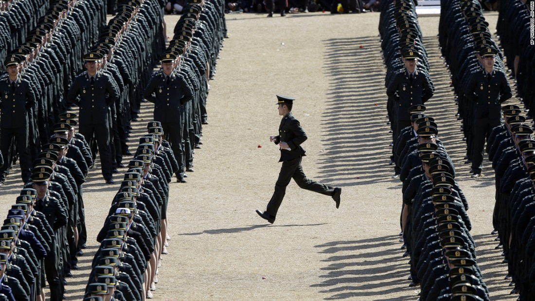 MARCH 12 - GYERYONG, SOUTH KOREA: A military officer runs to his position during the joint commission ceremony of thousands of new military officers of the army, navy, air force and marines at the military headquarters.