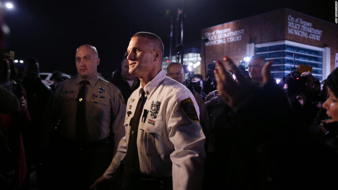"St. Louis County police Lt. Jerry Lohr walks through a crowd of protesters in Ferguson on March 12, trying to get them to move out of the street. The St. Louis County police said it had assumed ""command of the security detail regarding protests,"" together with the Missouri State Highway Patrol."