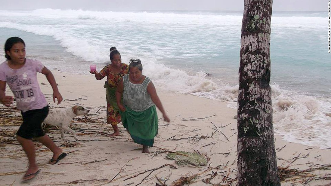 People move away from the beach March 13 on the island of Kiribati.