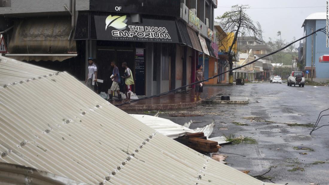 People walk past debris scattered on a street in Port Vila, Vanuatu, on Saturday, March 14.