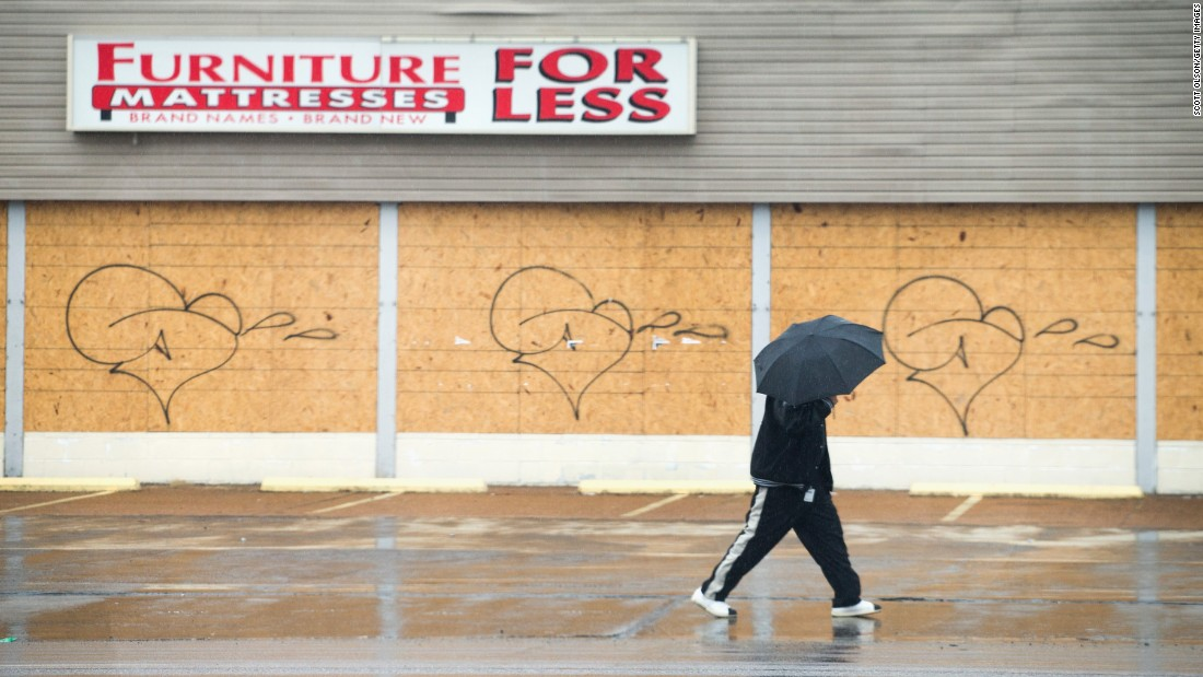 A pedestrian walks past a boarded-up furniture store March 13 in Ferguson. Some businesses in the city haven't reopened since last fall's riots, though a number continue to operate despite being boarded up.