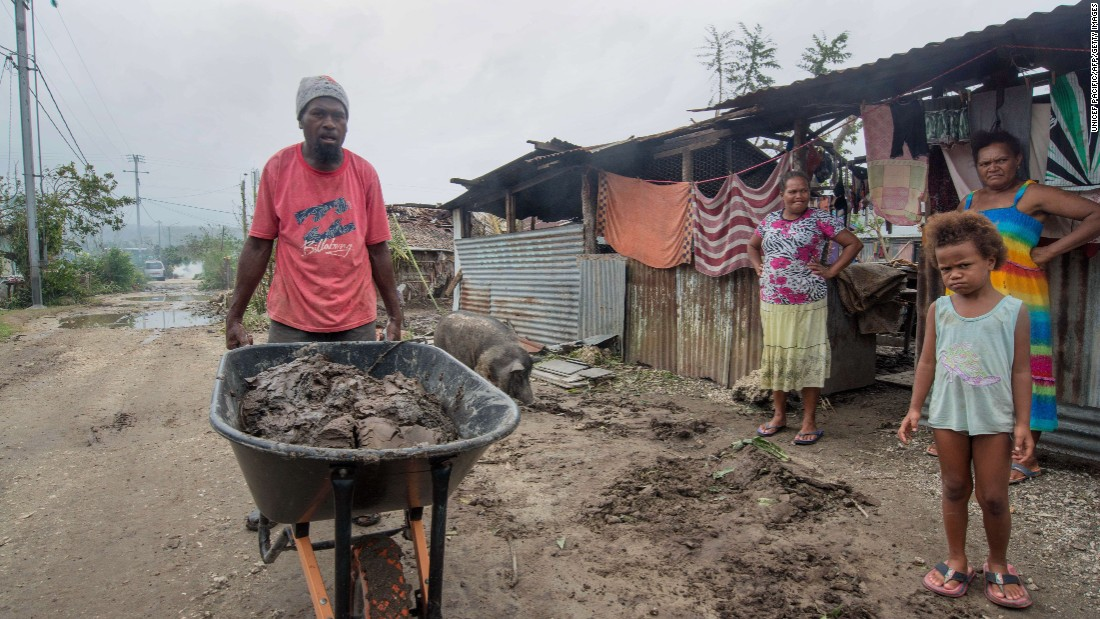 A resident clears mud and other debris outside homes near Port Vila  on March 15.