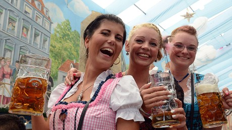 Girls dressed in typical Bavarian Dirndl dresses pose with beer mugs in a festival beer tent of the Oktoberfest beer festival at the Theresienwiese in Munich.