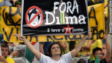 A demonstrator holds a banner reading 'Dilma out and take the Workers Party with you' during a rally to protest against the government of president Dilma Rousseff in Paulista Avenue in Sao Paulo Brazil on 15 March 2015. Thousands of demonstrators clad in the yellow-green national colours protested Sunday in several cities of Brazil against president Dilma Rousseff who is facing a complex economic panorama and a political corruption scandal.