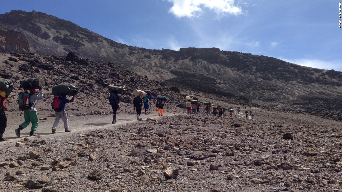 It takes a village to climb Kilimanjaro. Tanzanian porters carry tents, toilets and food up the mountain for hikers unaccustomed to the thin air. Mount Kilimajaro is the tallest peak in Africa, rising 19,340 feet (5,895 meters) above sea level.
