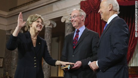 Senator Warren (Left) participates in a ceremonial swearing-in with her husband Bruce Mann and Vice President Joe Biden in the Old Senate Chamber on January 3, 2013 in Washington, DC.