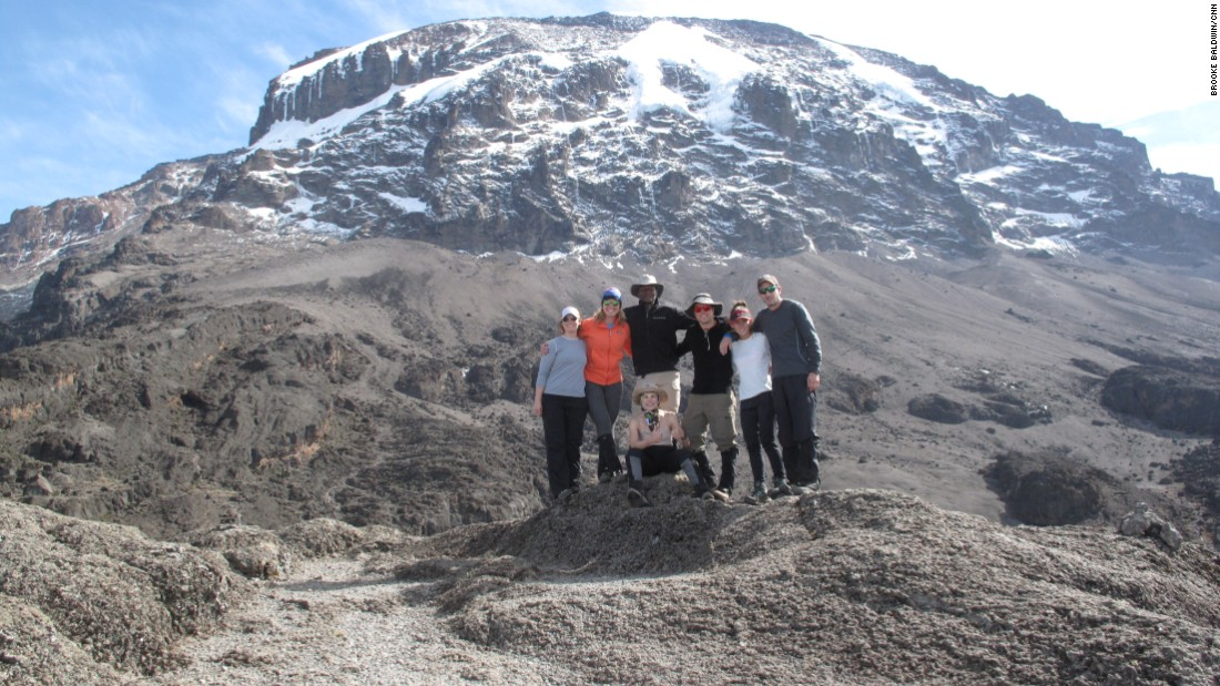 The six Americans in Brooke's group pose with guide Dismass in front of majestic Kilimanjaro.