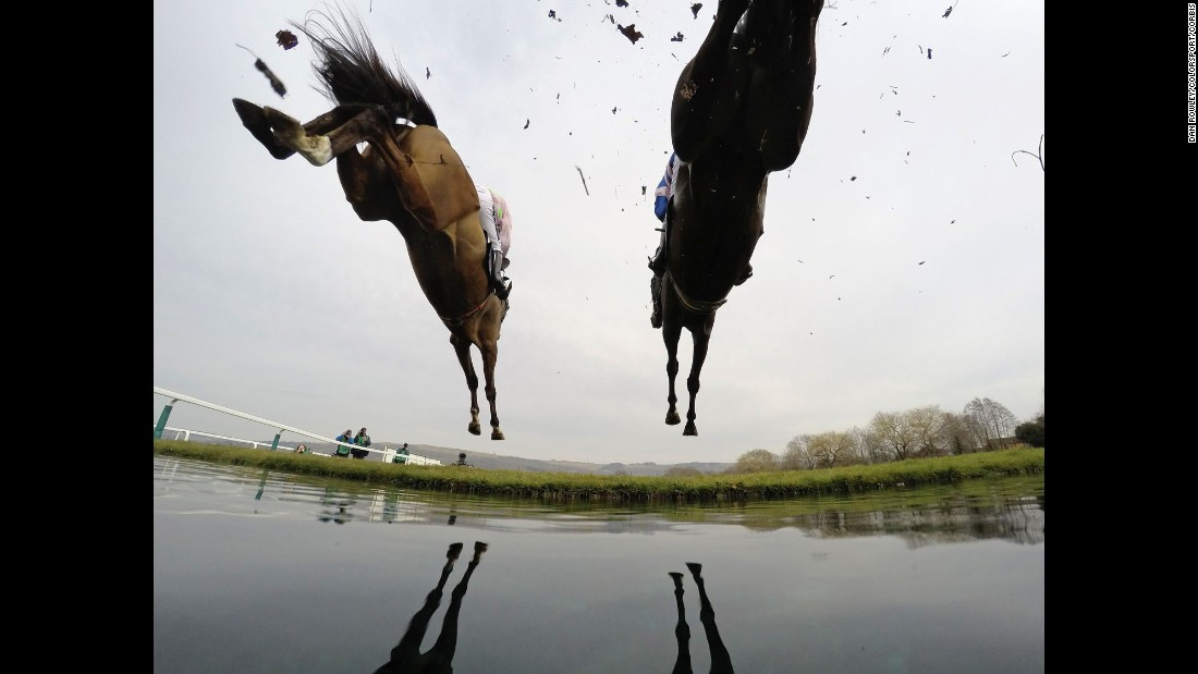 Horses clear water during a steeplechase race in Cheltenham, England, on Thursday, March 12.