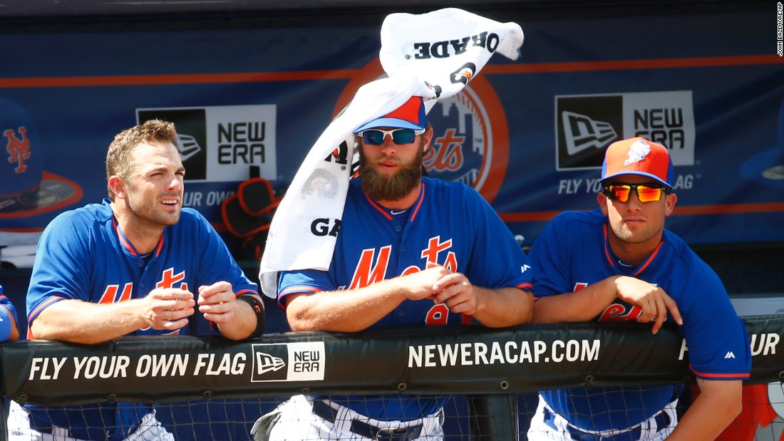 Wind blows a towel off New York Mets left fielder Kirk Nieuwenhuis as he watches a spring training game Thursday, March 12, in Port St. Lucie, Florida.