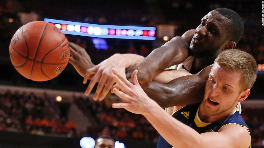Michigan's Max Bielfeldt, bottom, and Illinois' Nnanna Egwu battle for a rebound during a Big Ten tournament game Thursday, March 12, in Chicago.