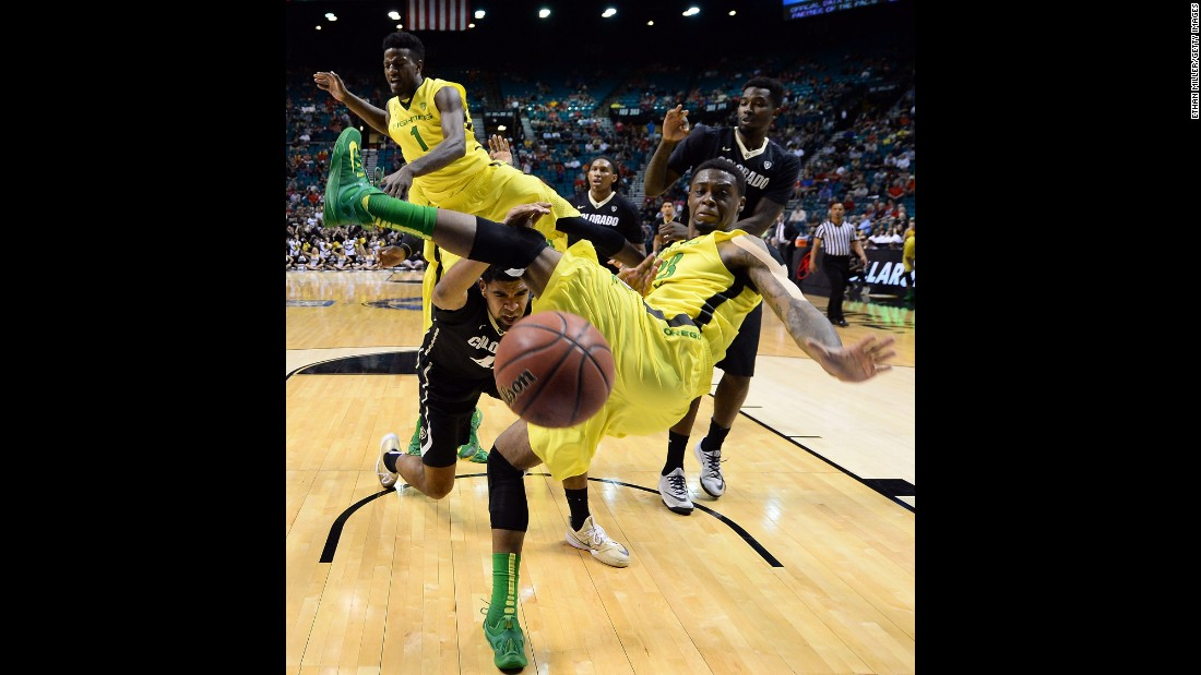 Oregon's Elgin Cook, foreground, loses his balance while defending the basket Thursday, March 12, during a Pac-12 tournament game against Colorado.