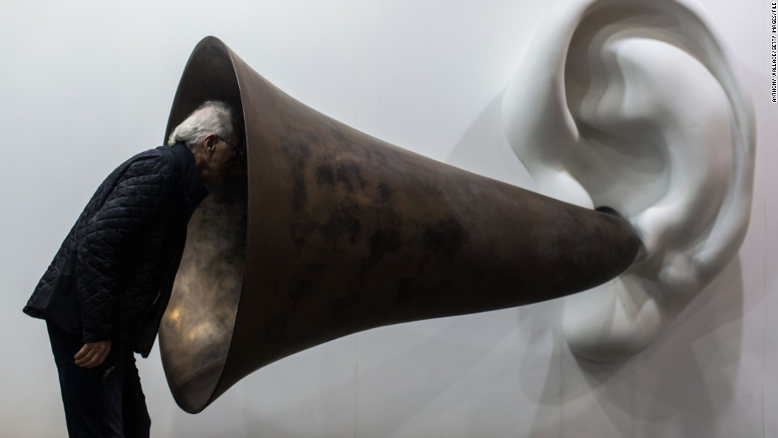 "It wasn't the only mind-bending artwork on show at the three-day fair. Here, a visitor inspects American artist John Baldessari's ""Beethoven's Trumpet (With Ear) Opus # 133."""