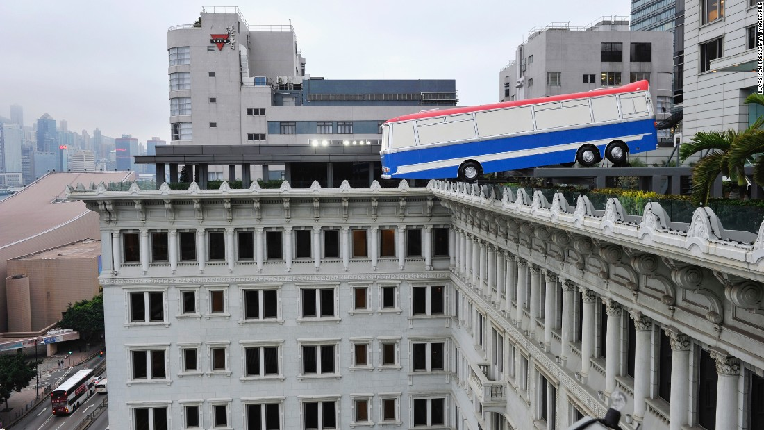 "Outside of the fair, Hong Kong city is dotted with fantastical works. Here, Richard Wilson's replica bus teeters on the edge of the Peninsula Hotel. The sculpture is called ""Hang on a Minute Lads; I've Got a Great Idea."""