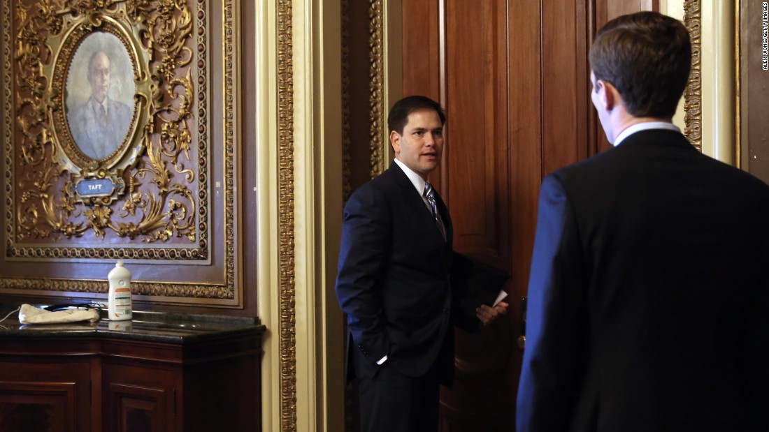 Rubio speaks to an aide on Capitol Hill as he arrives for the weekly Senate Republican Policy Committee luncheon in September 2013.