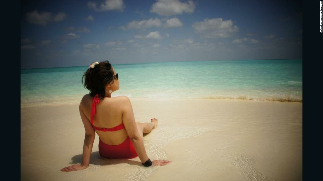 "<a href=""http://ireport.cnn.com/docs/DOC-1222529"">iReporter Adam Fredeus</a> snapped this photo of his girlfriend during a day-trip to a sandbank near Hanimaadhoo in the Maldives. Fredeus, who lives in Antwerp, Belgium, said that by staying in smaller, less expensive local resorts, they were able to experience the Maldives ""in a natural way with knowing the locals and understanding their culture."" The Republic of Maldives is an independent island nation of nearly 1,200 islands and sandbanks in the Indian Ocean."