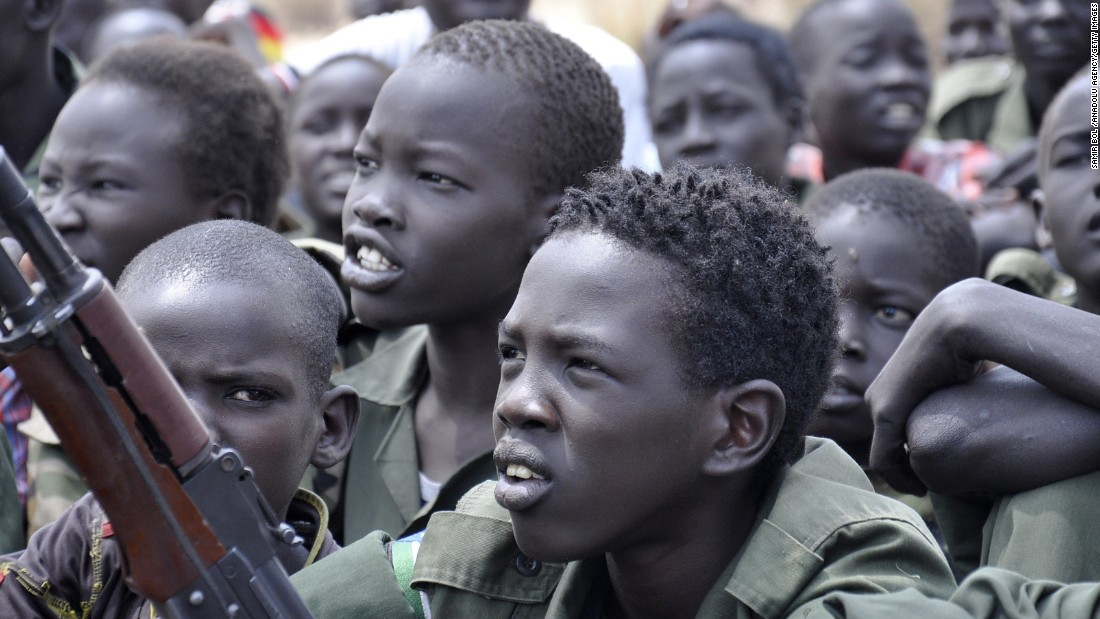 Children sit with their rifles at a ceremony taking place in South Sudan on the issue of the disarmament, demobilization and reintegration of child soldiers. The process was overseen by UNICEF and partners in February 2015.