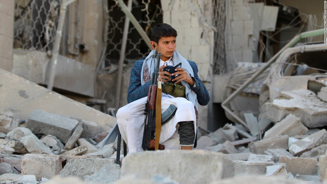 An armed Yemeni youth sits amid the rubble in December 2014, guarding the damaged house of the Iranian ambassador in the capital Sanaa.