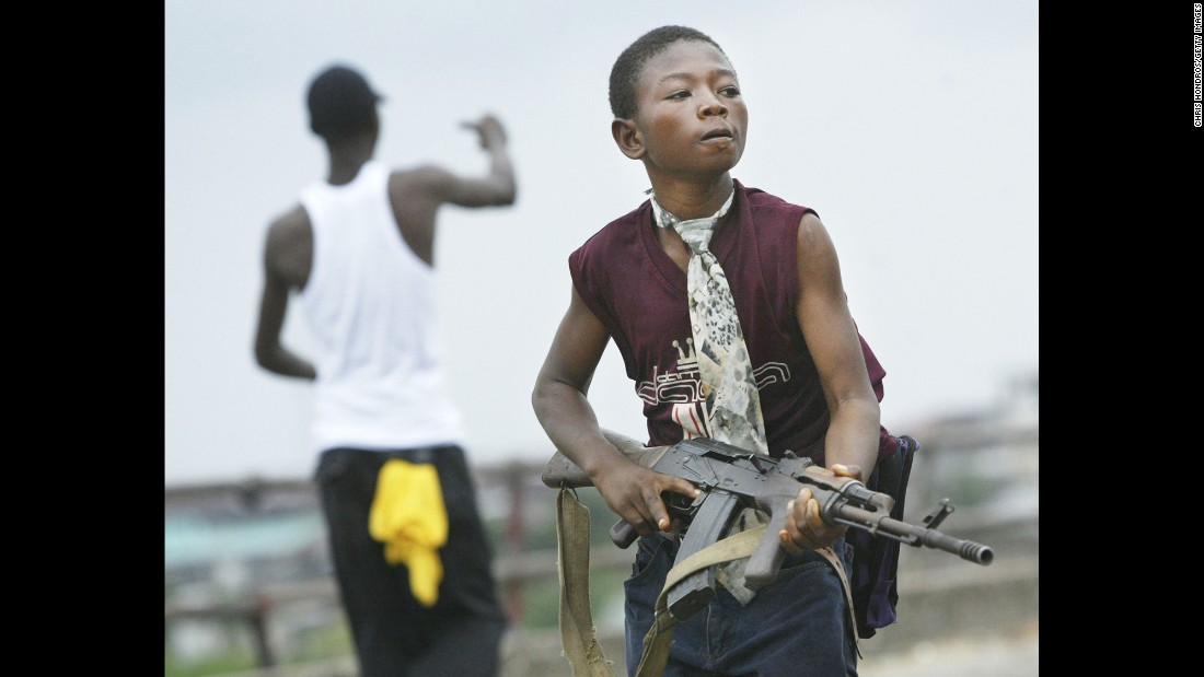 A Liberian militia child loyal to the government walks away from firing on rebel forces across a key bridge while another taunts them in Monrovia in 2003.