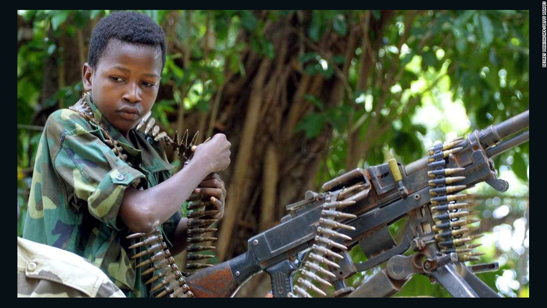 A Chadian child soldier stands in front of a machine gun at De Roux camp in Bangui, Central African Republic, in 2003.