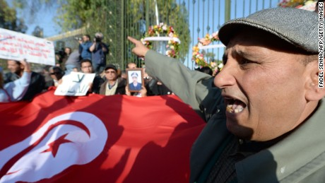 Tunisians wave the national flag as they protest outside the National Bardo Museum in Tunis on March 19, 2015, a day after the attack on the national museum.