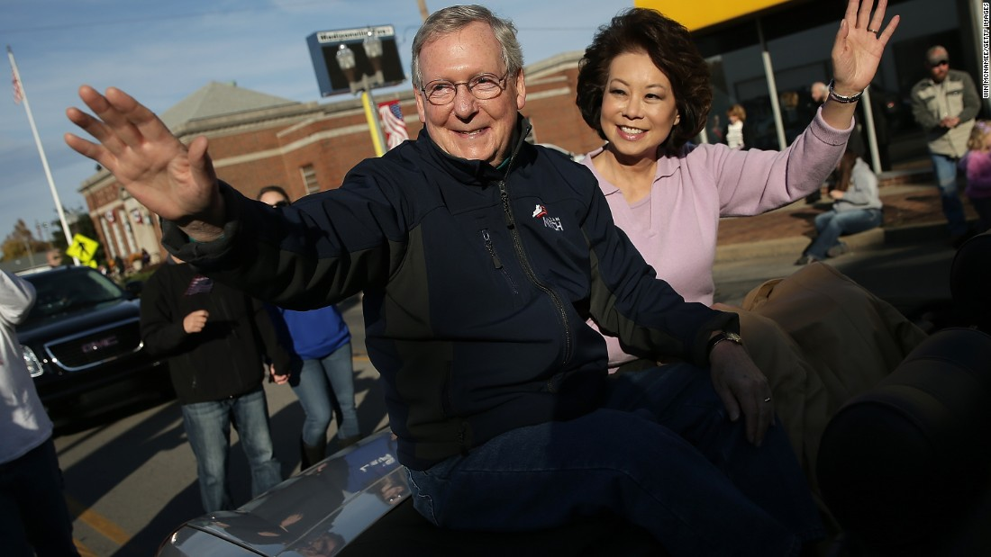 McConnell waves to a crowd while riding with his wife, Elaine Chao, in the Hopkins Country Veterans Day Parade in November 2014 in Madisonville, Kentucky.