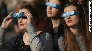 People look into the sky near the Brandenburg Gate in Berlin, Germany.