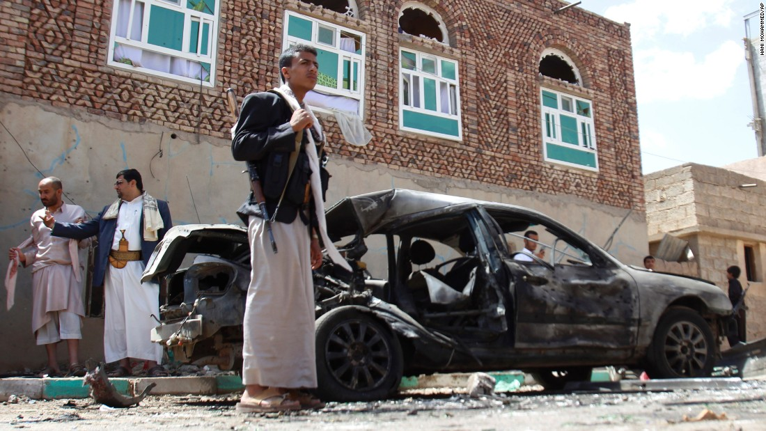 Houthi fighters stand near a damaged car after bombings in Sanaa on March 20. The attacks started with suicide bombings inside the buildings, followed shortly by explosions outside, two senior Houthi leaders said.