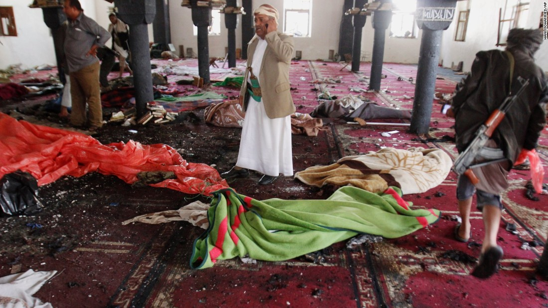 People stand amid bodies covered with blankets in a mosque after a suicide attack in Sanaa on March 20.